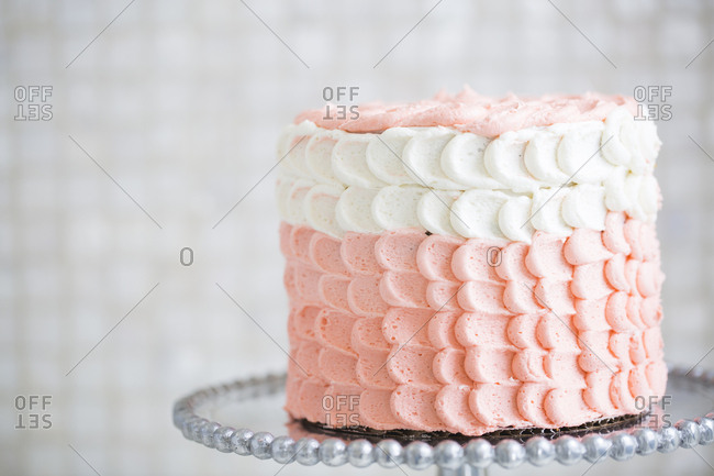 Close-up of a pink and white cake with scalloped frosting