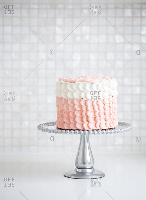 Cake with pink and white scalloped frosting