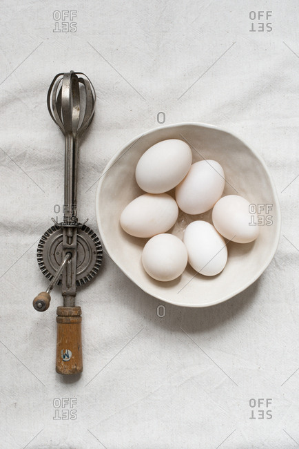 A bowl of six white eggs with a whisk