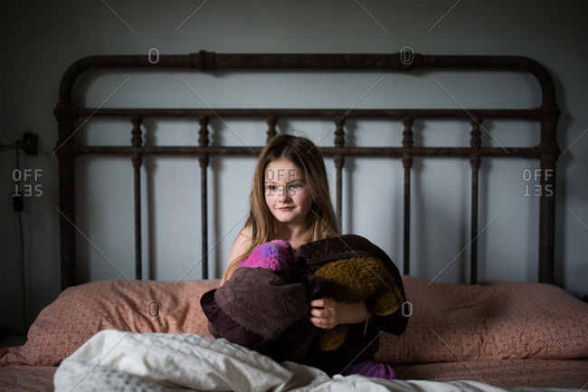 Young girl sitting on bed holding a fuzzy blanket