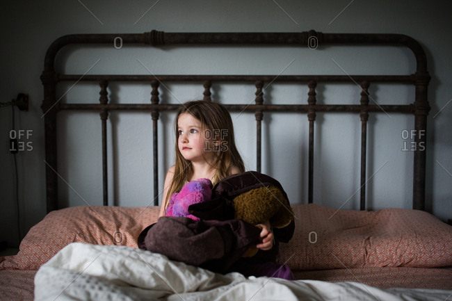 Little girl sitting on bed holding a fuzzy blanket