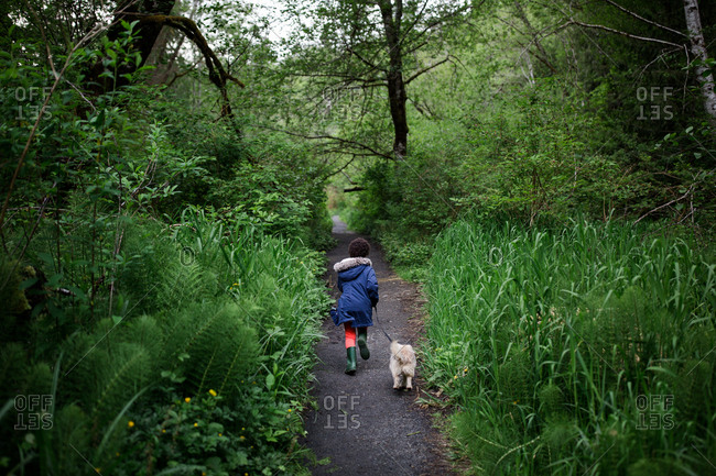 Girl walking dog on trail surrounded by green foliage