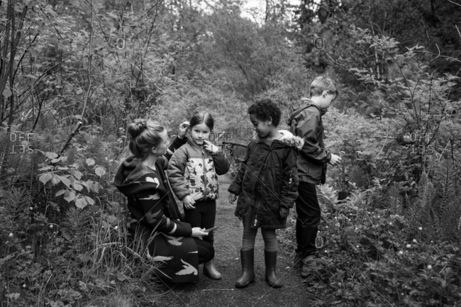 Family stopped on a path in the woods in black and white
