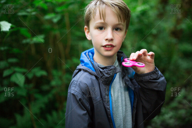 Boy playing with pink fidget spinner