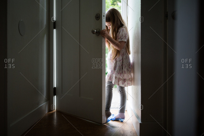 Little girl standing in doorway wearing toy high heels