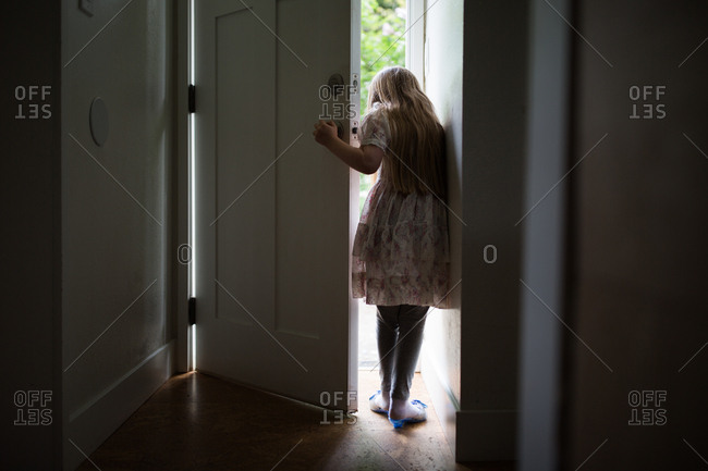 Rear view of girl standing in doorway wearing toy high heels