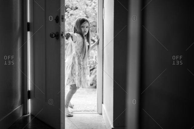 Little girl wearing toy high heels and closing door behind her
