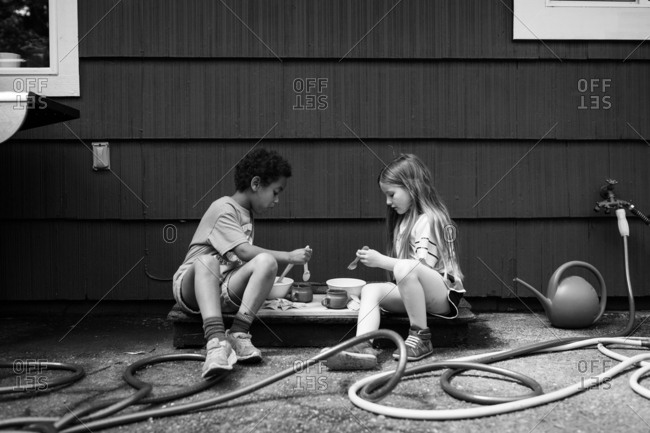 Two girls having snack outdoors in black and white