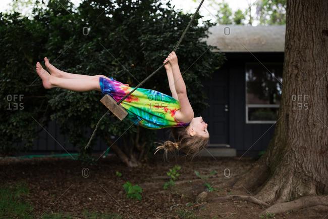 Girl wearing tie-dyed dress swinging on a tree swing