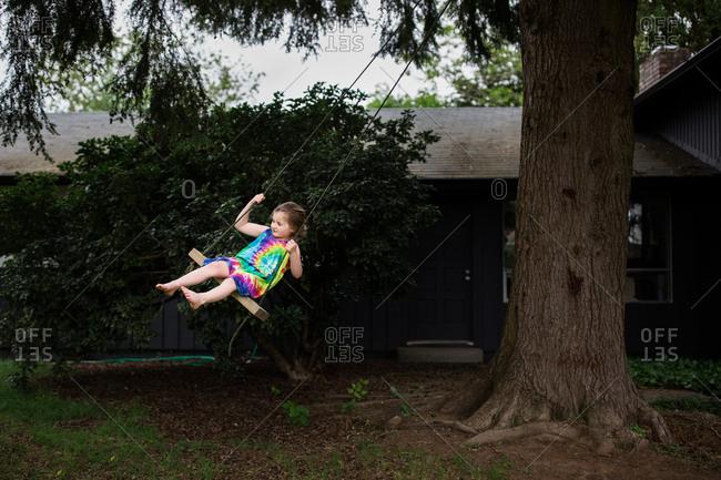 Girl wearing tie-dyed dress swinging on a backyard tree swing