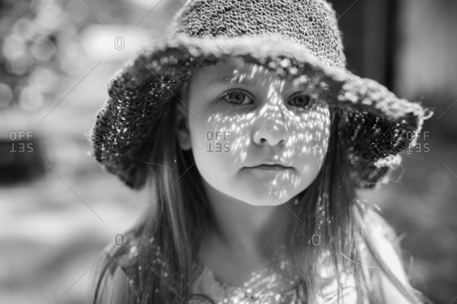 Young girl wearing sun hat with dappled light on her face