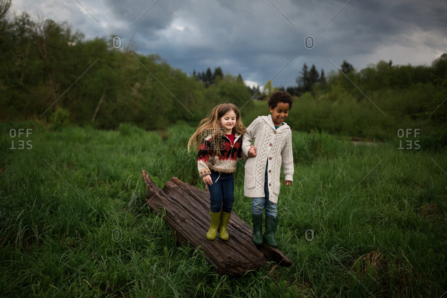 Two girls holding hands and standing in a log on a field