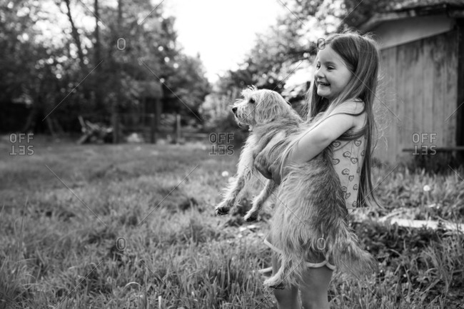 Girl carrying a furry dog outside