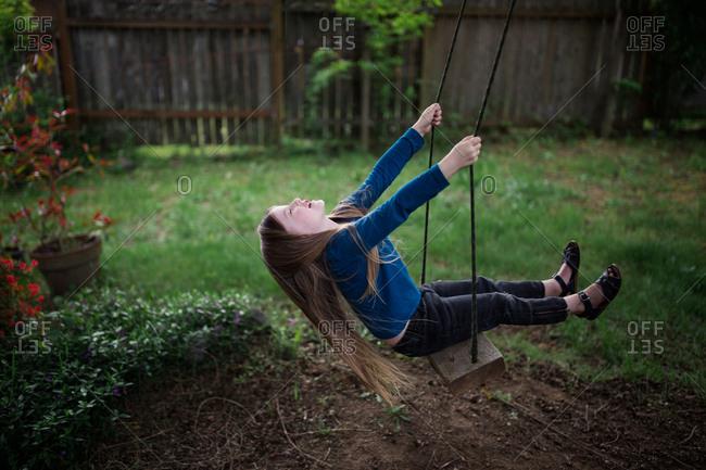 Girl swinging on a tree swing