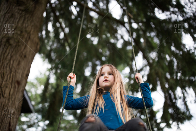 Low angle view of girl swinging on a tree swing