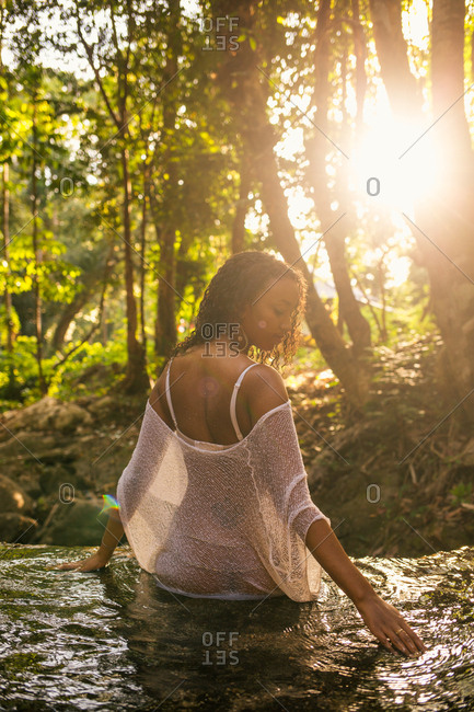 Young woman in see-through cover-up sitting on waterfall