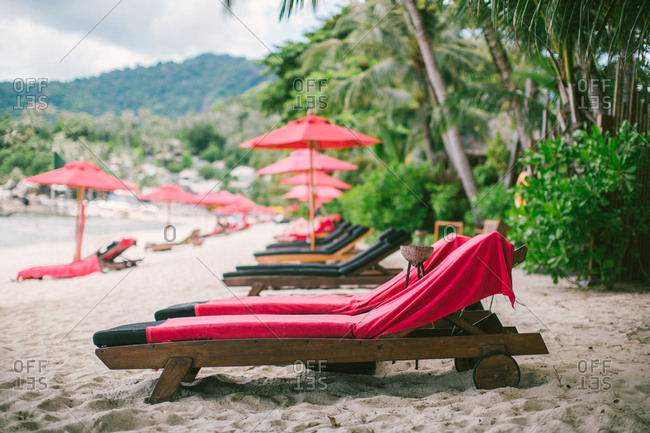 Red lounge chairs and umbrellas on a beach
