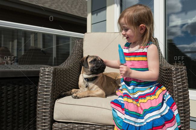 Girl eating popsicle by dog on patio chair