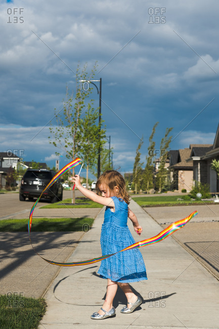 Young girl twirling ribbon on sidewalk