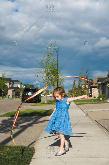 Girl twirling ribbon on sidewalk