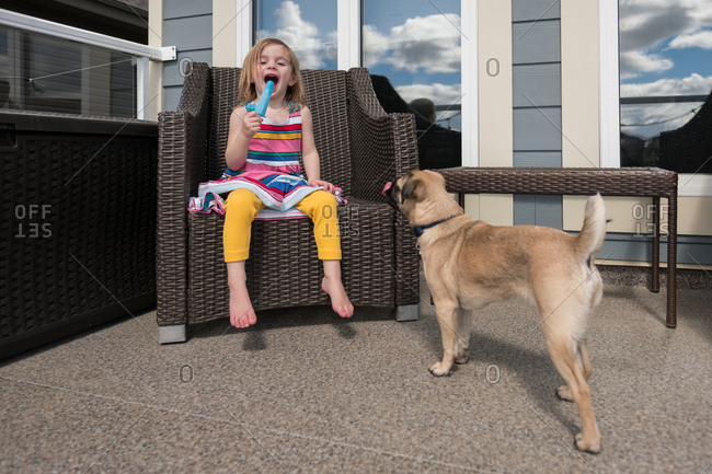 Little girl eating popsicle while pug dog watches