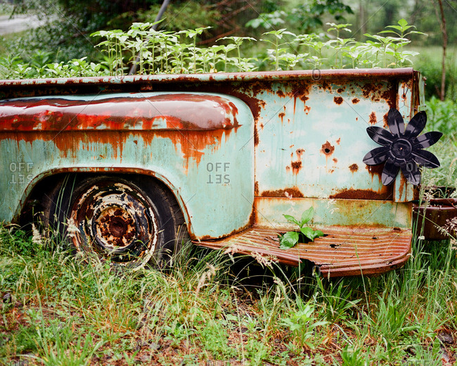 Abandoned rusted trailer overgrown with weeds