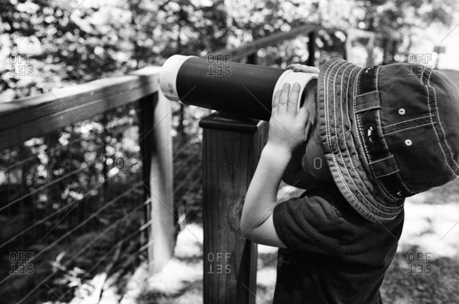 Child looking through telescope at scenic vista