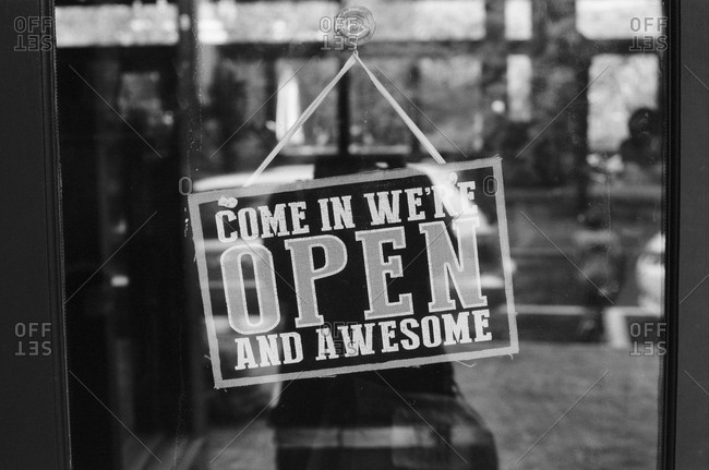 Open sign hanging on glass door