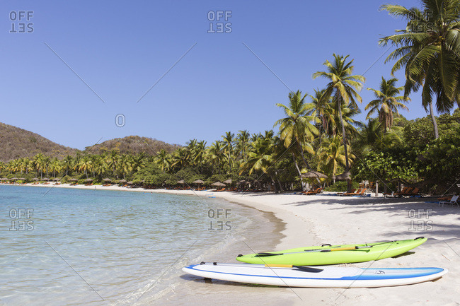Virgin Gorda, British Virgin Islands - May 13, 2015: View of surf boards and chairs on the tropic beach
