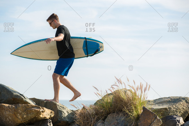 Young man carrying surfboard on large rocks