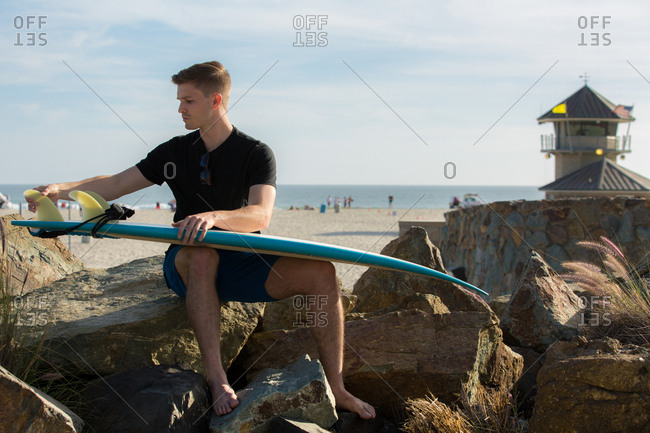 Young man inspecting surfboard on large rocks