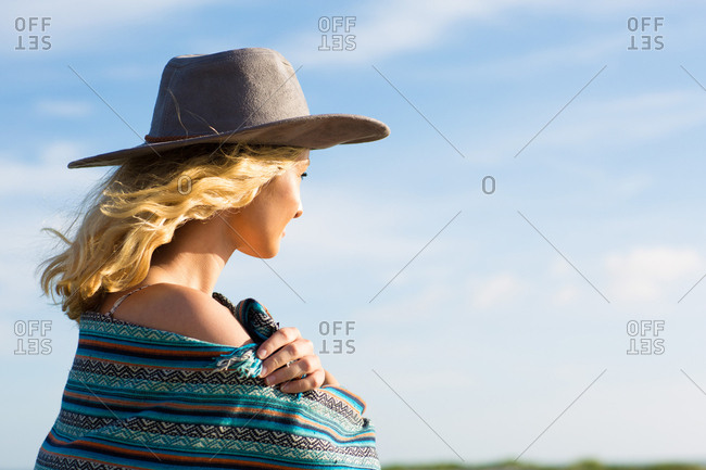 Young woman in hat looking out to sunset
