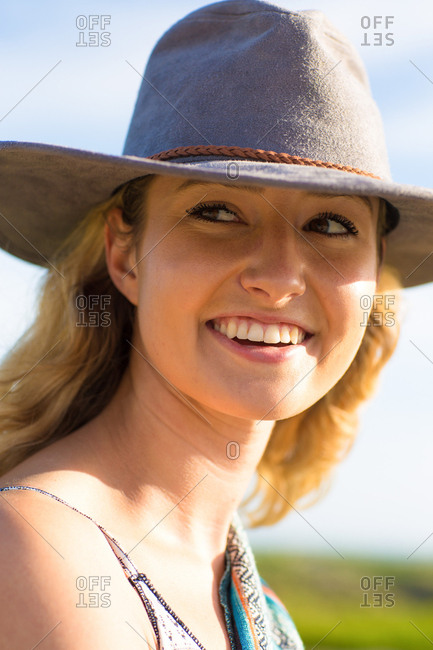 Happy young woman in hat at sunset
