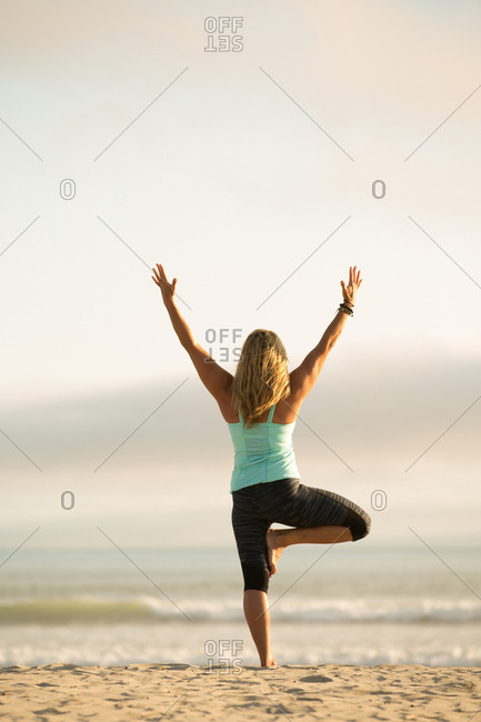 Blonde woman practicing yoga lunge on a beach