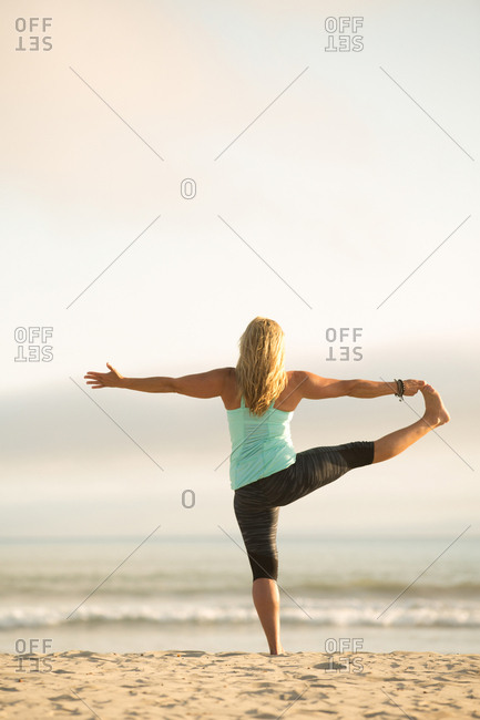 Blonde woman doing yoga lunge on a beach