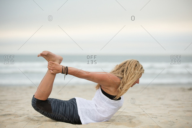 Blonde woman doing yoga pose by the ocean