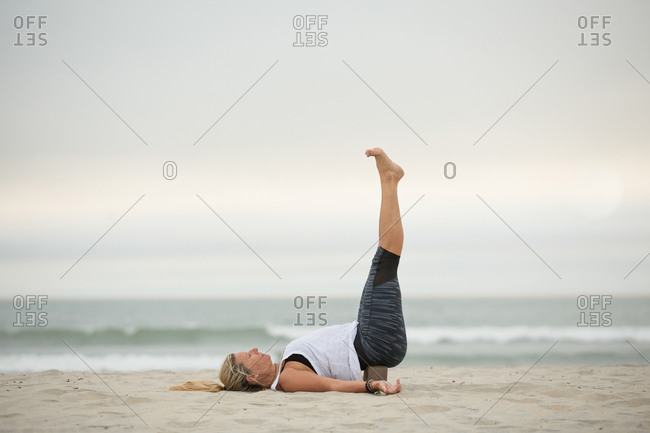 Woman doing yoga pose with feet in the air on a beach