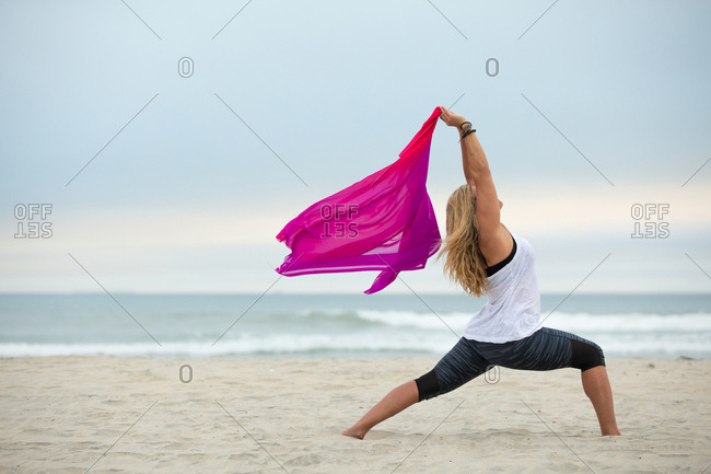 Blonde woman doing yoga pose with pink scarf on a beach