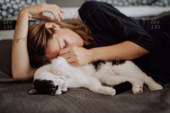 Woman lounging with cat on bed