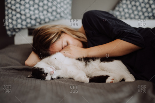 Woman asleep with her cat on bed