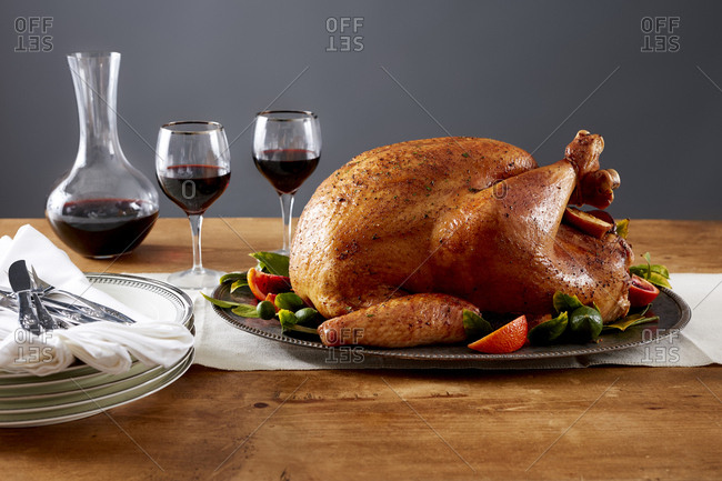 Roasted turkey on platter with two glasses of wine