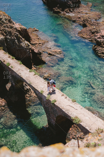Peniche, Portugal - February 4, 2017: Couple crossing coastal footbridge