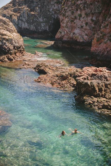 Peniche, Portugal - February 4, 2017: Couple swimming in coastal waters