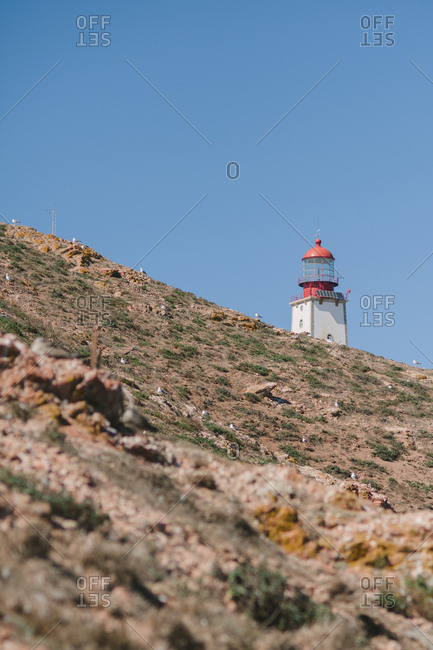 Lighthouse by hill in Portugal
