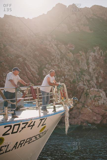 Peniche, Portugal - February 4, 2017: Two men on boat in coastal waters