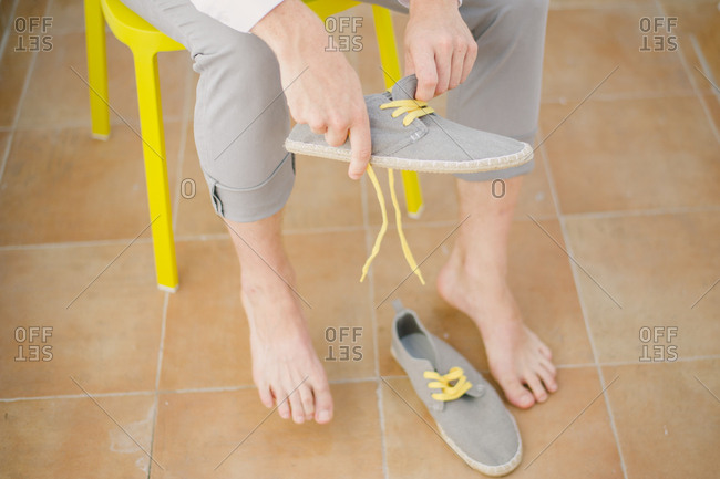 Groom putting on casual shoes