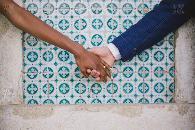 Engaged couple holding hands by tiled wall