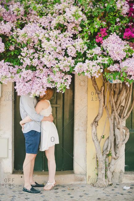 Couple hugging behind flowering tree