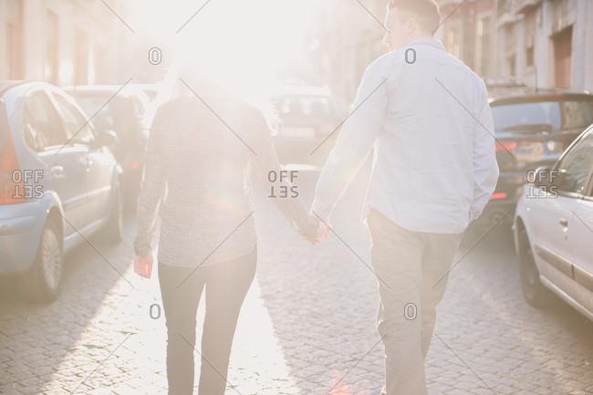 Lisbon, Portugal - February 4, 2017: Couple walking in sun dappled street