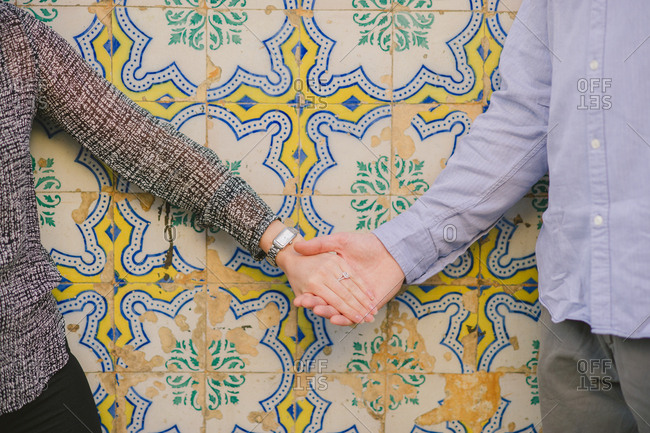 Engaged couple holding hands by tiles